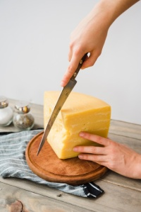 close-up-person-cutting-cheese-with-knife-round-chopping-board_23-2148166558